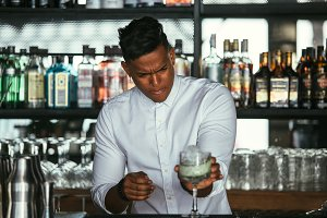 Concentrated bartender makes cocktai