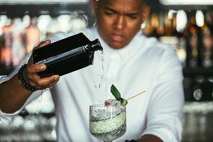 Bartender adding alcohol