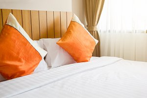 orange pillow and white blanket