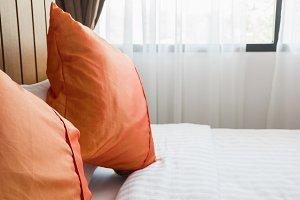 orange pillow and white blanket