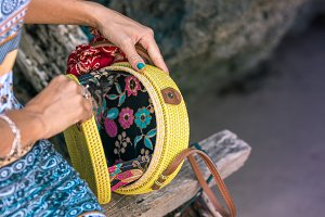 Woman hands with fashionable stylish yellow rattan bag outside. Tropical island of Bali, Indonesia. Rattan and silk.