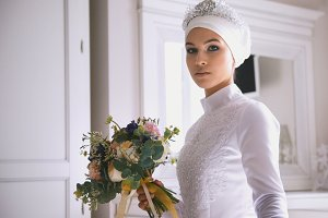 Muslim bride in white wedding dress holding the bouquet of flowers in hand
