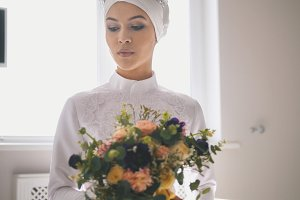 Portrait of young woman in traditional islamic wedding dress holding the bouquet of flowers