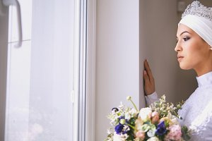 Beautiful muslim bride looking out the window holding the bouquet of flowers