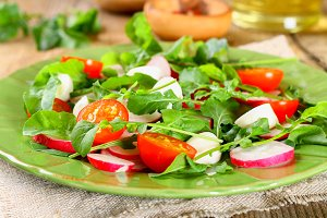 Vegetarian salad of arugula, tomato, radish and mozzarella cheese on an old wooden table.