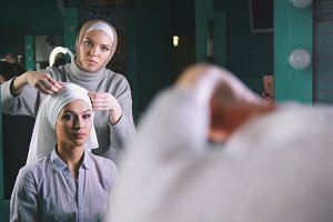 Muslim young woman preparing islamic wedding headdress for young bride in front of mirror
