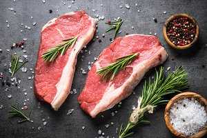 Raw beef striploin steak with herbs and spices.