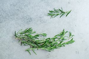 Flatlay with rosemary sprigs arranged on metallic background