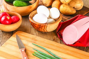 Ingredients for okroshki - sausage, eggs, radishes, onions, potatoes, cucumbers on an old wooden table.