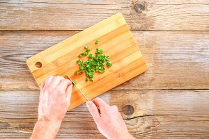 Male hands cut a green onion on a cutting board on an old wooden table.