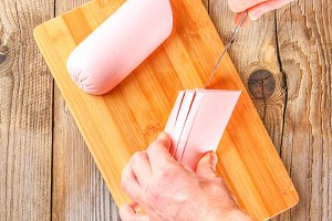 Men's hands cut the Bolognese sausage on a cutting board on an old wooden table.