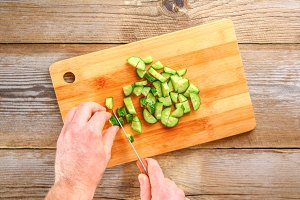 Men's hands cut the light for okroshki on a cutting board on an old wooden table.