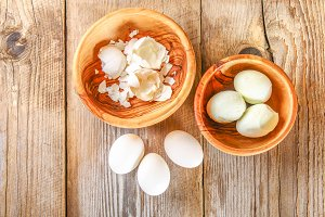 Boiled chicken eggs and their shells in wooden bowls on an old wooden table.