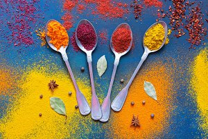 A variety of bright spices with spoons on a blue background. View from above.