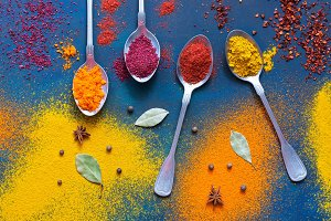 Spices with spoons on a blue background. Bright multicolored background of spices. Top view.