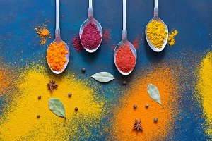 A variety of multicolored spices with spoons on a blue background. Top view, copy space.