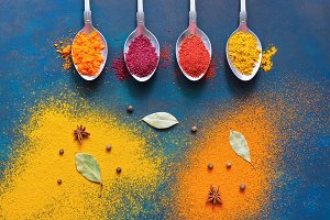 Bright background of multi-colored spices in spoons. A top view, a place for your text or advertising.