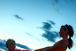 fit mother and child on seashore on sunset having fun time
