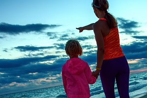 mother and child on seacoast on sunset pointing at something