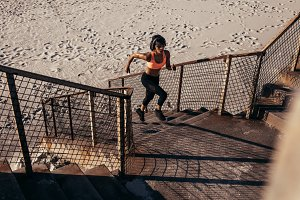 Athletic woman runs up the steps
