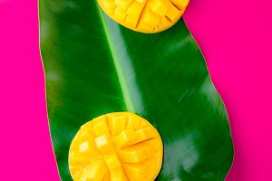 Creative layout made of summer tropical fruits mango and tropical leaves on pink background. Flat lay. Tropical food concept.