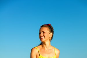 smiling active woman on seashore in evening walking