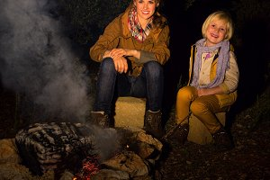 mother and daughter travellers sitting near camping fire