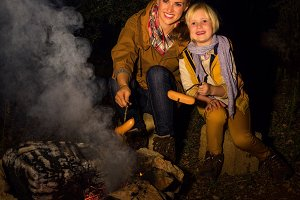 mother and daughter travellers near campfire grilling sausages