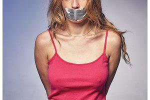 Young woman with his mouth glued with tape.