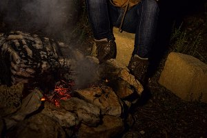 smiling healthy traveller woman sitting near bonfire