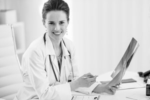 Portrait of happy doctor woman holding fluorography in office