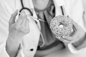 Closeup on medical doctor woman making injection using diabetes syringe into donut
