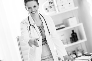 Smiling medical doctor woman in office stretching hand for hands
