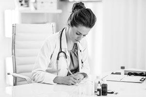 Medical doctor woman writing prescription