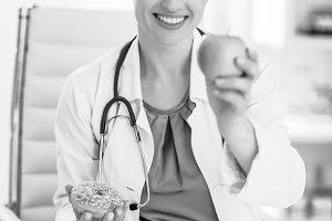 Happy medical doctor woman giving apple instead of donut