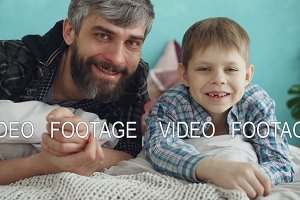 Close-up portrait of two people adult father and cute little son lying on bed at home and smiling. Paternal love, parenthood and happy family concept.