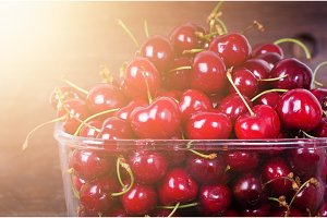 Sweet red cherries in glass bowl on dark wooden backgound with copy space. Sunny summer and harvest concept. Sunlight effect. Vegan, vegetarian, raw food
