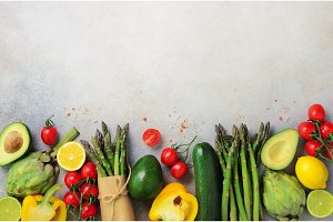 Different organic vegetables - asparagus, tomatoes cherry, avocado, artichoke, pepper, lime, lemon, salt on gray background. Food fame with copy space, top view. Raw, vegan, vegetarian concept.