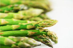 Green fresh asparagus on gray background. Top view. Raw, vegan, vegetarian and clean eating concept.