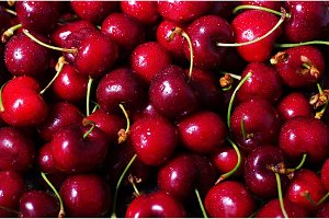 Red cherries background with water drops. Top view. Summer and harvest concept. Vegan, vegetarian, raw food