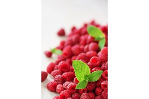 Fresh organic raspberries with mint leaves. Fruit background with copy space. Summer and berries harvest concept. Vegan, vegetarian, raw food.