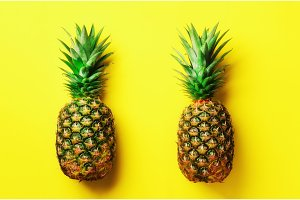Fresh pineapples on yellow background. Top View. Pop art design, creative concept. Copy Space. Bright pineapple pattern for minimal style.