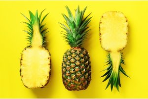 Half slice of fresh pineapple and whole fruit on yellow background. Top View. Copy Space. Bright pineapples pattern for minimal style. Pop art design, creative concept