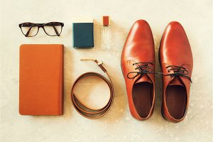 Men's accessories and shoes on gray background. Flat lay of elegant belt, glasses, parfume, notebook. Stylish set and fashion concept for man.