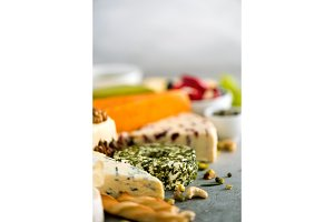 Assortment of hard, semi-soft and soft cheeses with olives, grissini bread sticks, capers, grape, on grey concrete backgound. Top view, copy space, flat lay. Cheese selection appetizer plate.