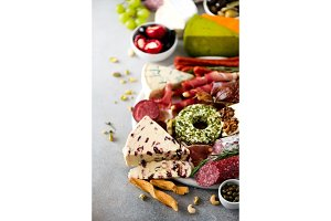 Traditional italian antipasto, cutting board with salami, cold smoked meat, prosciutto, ham, cheeses, olives, capers on grey background. Cheese and meat appetizer.