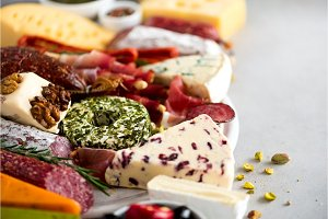 Traditional italian antipasto, cutting board with salami, cold smoked meat, prosciutto, ham, cheeses, olives, capers on grey background. Cheese and meat appetizer