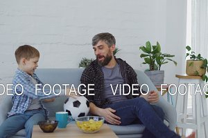 Cheerful loving father is playing with his little son throwing and kicking football and eating snacks in light apartment. Happy family and sport concept.