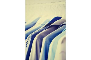 Male clothes, jackets and shirts hanging on clothes rail. Blue color clothes. Copy space. Image with toned effect