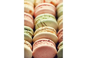 Colorful french macaroons flat lay. Pastel colors pink, green, yellow macarons with copy space, top view. Holidays and celebrations concept. Sweet gift for woman, girl